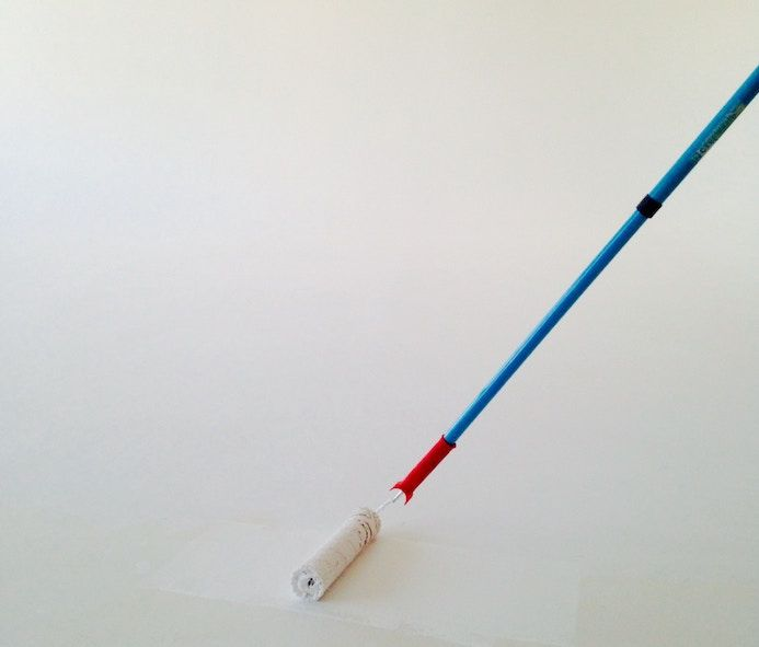 Painter roll with white color against white wall to represent problem solving in software engineering.
