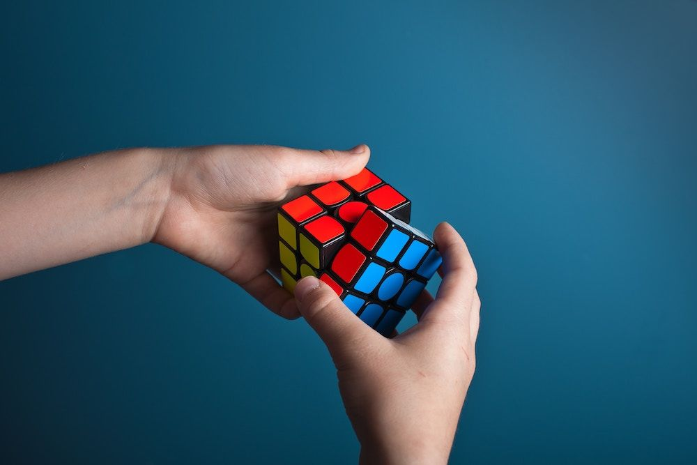 Person solving a rubiks cube representing problem solving